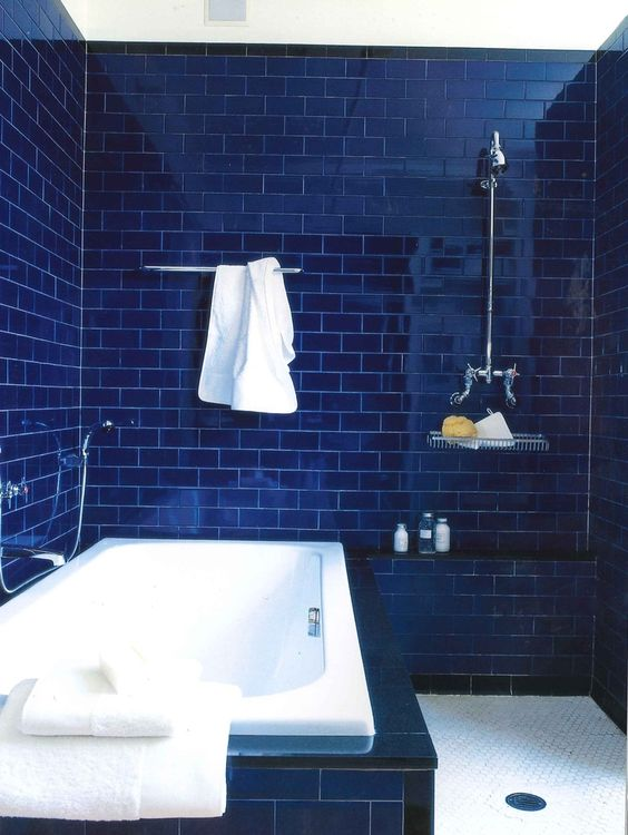 a deep blue bathroom fully clad with subway tiles, a white tub and neutral fixtures for a chic look
