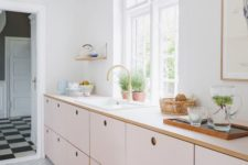 a delicate blush kitchen with only lower cabinets and white countertops plus much natural light