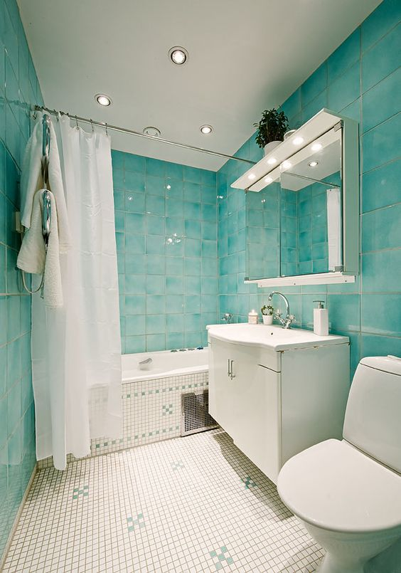 a dreamy bathroom with turquoise tiles, neutral ones, neutral furniture, white appliances built-in lights and a large mirror