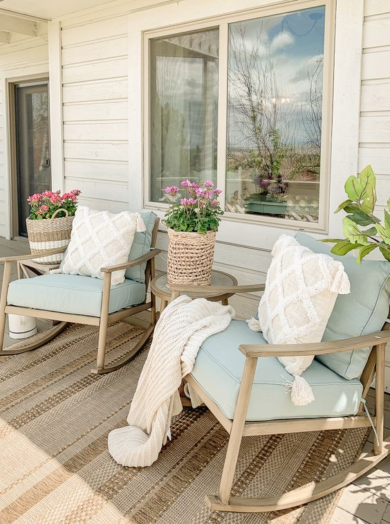 a farmhouse summer porch with wooden furniture, aqua upholstery, neutral pillows, blooms in woven plants is very welcoming