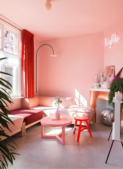 a glam living room with light pink walls and a ceiling, a pink sectional and a coffee table, a neon light and a red stool