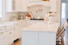 a glam white kitchen with stylish cabinets, a white marble tile backsplash and touches of brass and gold here and there