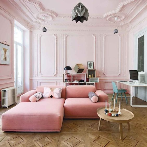 a gorgeous blush living room with molding, a pink sofa, a creative storage unit and a working space at the wall
