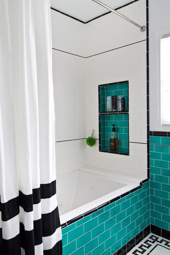 a graphic black and white bathroom with turquoise tile lining, with a niche and a black and white curtain