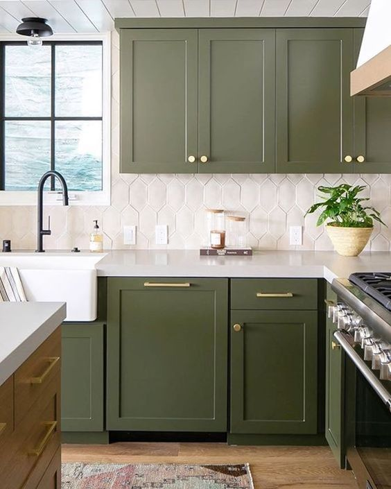 a grass green kitchen with gold and brass touches, black fixtures and a catchy geometric tile backsplash