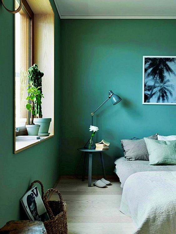 a green bedroom with some comfy furniture, green and grey bedding and potted cacti