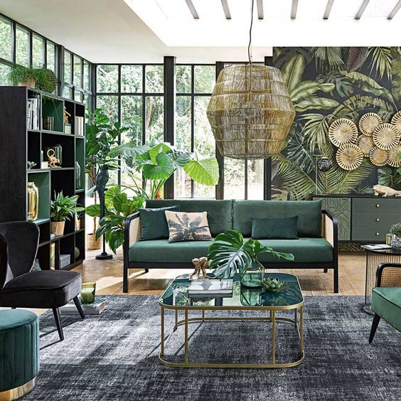 a jungle-themed living room with a tropical print wall, a green storage unit and hunter green furniture and potted plants