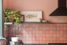 a kitchen with pink walls, a pink tile backsplash, dark green cabinets and black wooden countertops looks very catchy