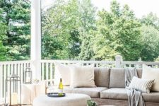 a large modern porch with neutral furniture, river stone ottomans, candle lanterns and neutral textiles