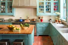 a light blue kitchen in vintage style, with neutral countertops, a large hood and kitchen island plus metal stools