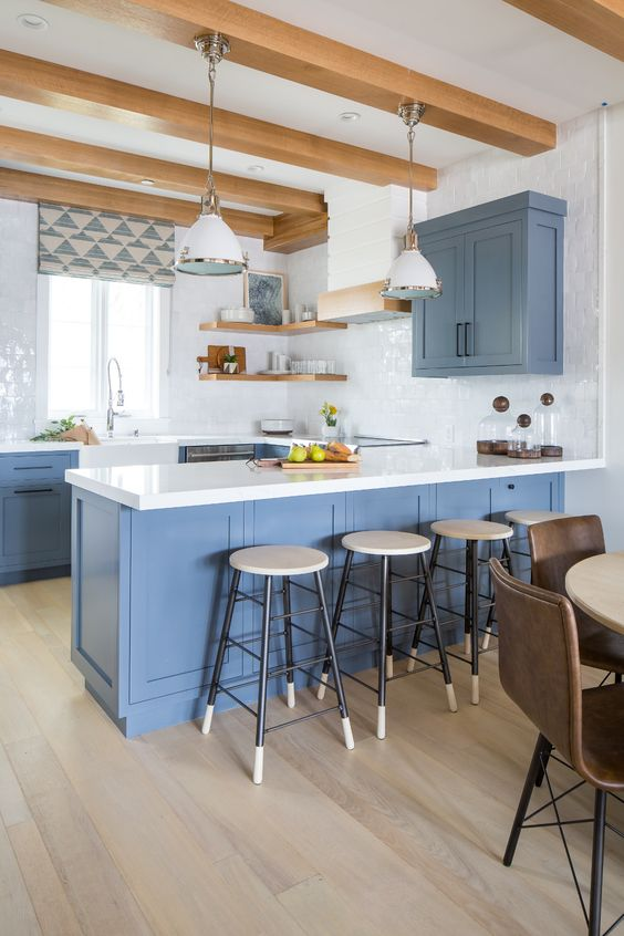 a light blue kitchen with white stone countertops and a white tile backsplash, open shelves and wooden beams is welcoming