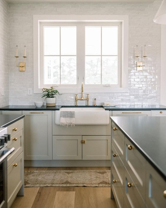 a light grey kitchen with black countertops, white tiles and gold and brass touches for a shiny touch