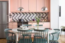 a light pink mid-century modern kitchen with a graphic tile backsplash and a dining zone in blue right here