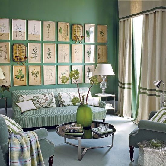 a lovely green living room with green walls, curtains and striped furniture, with a large vintage gallery wall