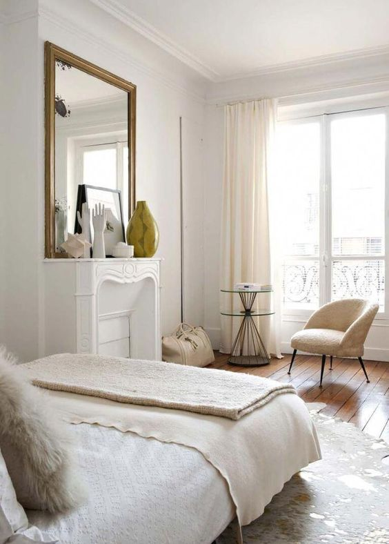 a lovely neutral Parisian bedorom with a faux fireplace, a statement mirror, a soft chair and a side table