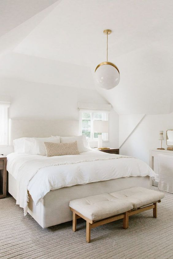 a lovely neutral bedroom with an upholstered bed, a neutral bench, wooden nightstands, a white vanity and a chair