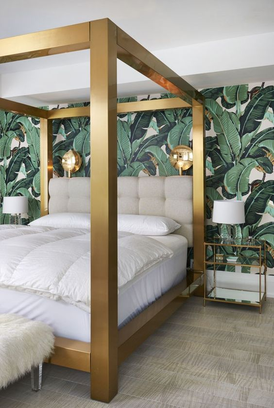a luxurious tropical space with a banana leaf wall, a solid gold bed, chic glass nightstands and sconces