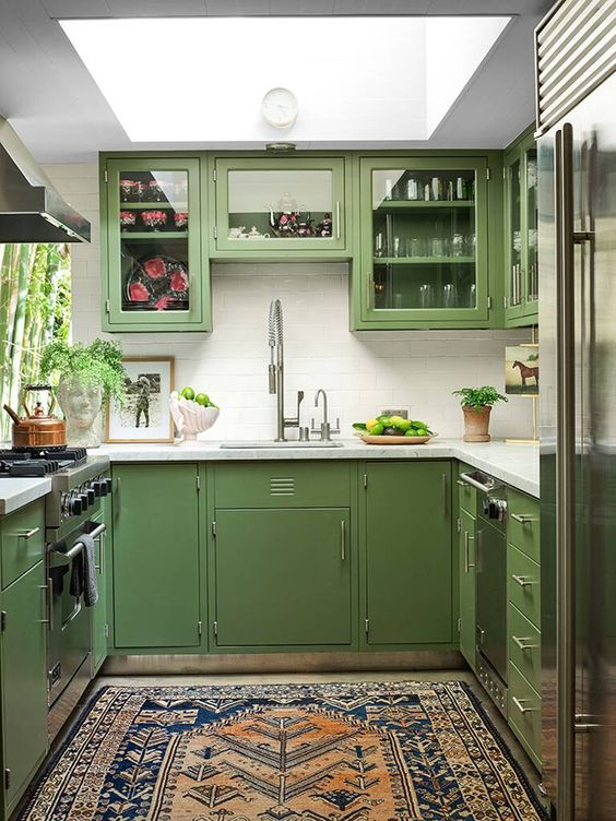 a mid century modern green kitchen with a skylight, a white tile backsplash and white countertops plus a printed rug
