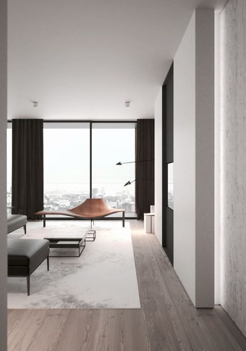 a minimal living room with a glazed wall, a leather chair, a modern table and a grey and black ottoman
