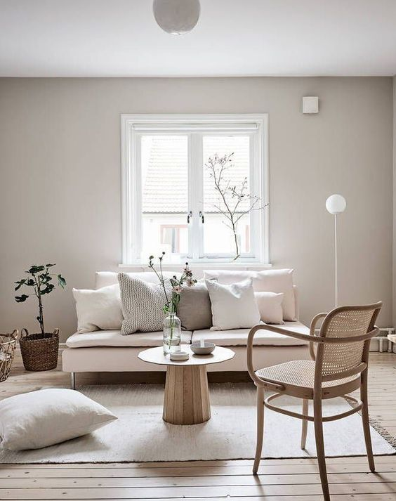 a minimal neutral living room with a blush loveseat, a rattan chair, neutral pillows and some greenery