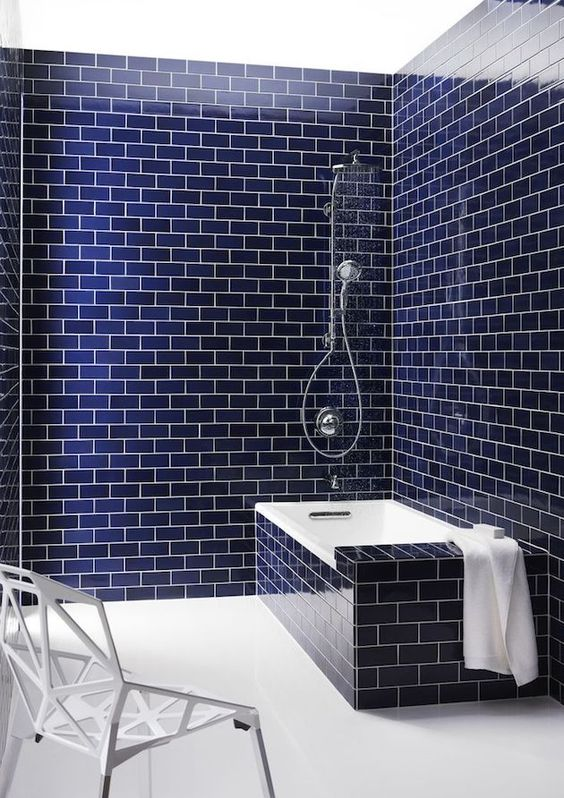 a minimalist bathroom clad with navy subway tiles and accented with white grout and items is extra bold