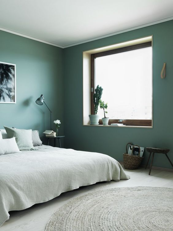 a minimalist bedroom with green walls, light green bedding and a large window that brings much natural light