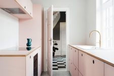 a minimalist blush galley kitchen with sleek cabinets and built-in appliances is very stylish and chic
