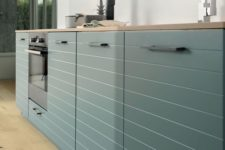 a minimalist hunter green kitchen with striped cabinets, butcherblock countertops and a matte glass backsplash