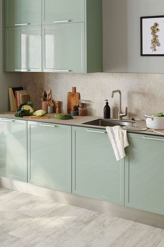 a minimalist kitchen in mint green, with sleek cabinets, a beadboard countertop and a plywood backsplash
