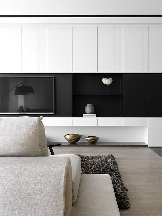a minimalist living room with a black and white wall, a built-in TV, neutral furniture and chic decor