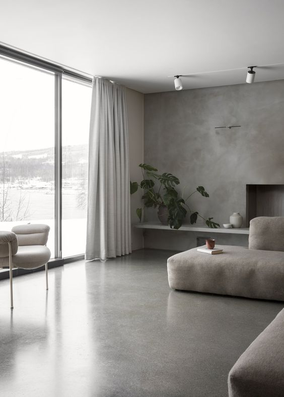 a minimalist living room with a concrete floor and wall, a grey sectional, a white chair and a glazed wall