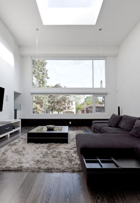a minimalist living room with a large skylight and window, a TV unit, a dark sectional sofa and a coffee table