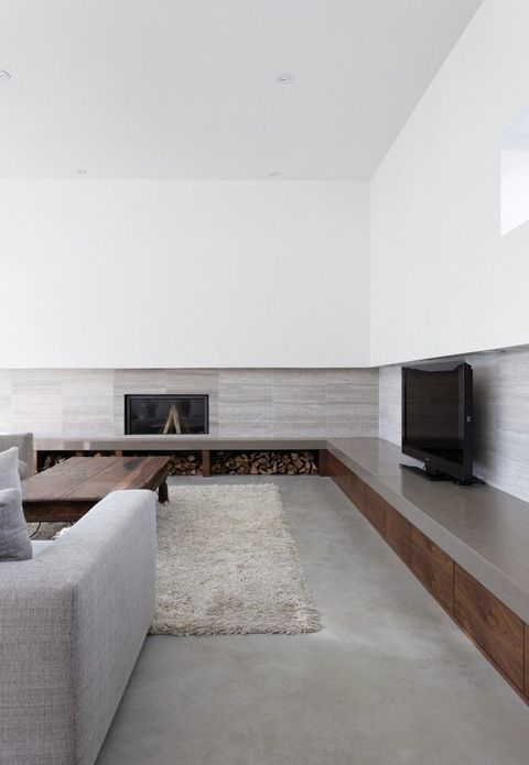 a minimalist living room with a long storage unit along several walls, a concrete floor, comfy furniture and touches of wood