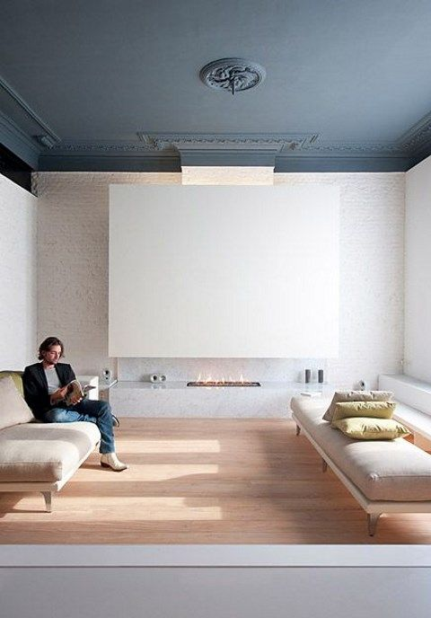 a minimalist living room with a refined black ceiling, a fireplace, some neutral furniture and yellow pillows