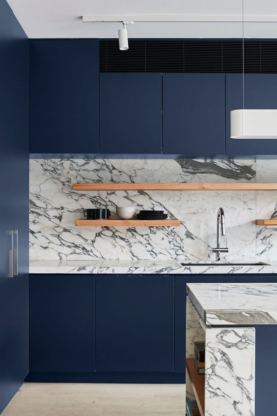 a minimalist navy kitchen with a neutral marble backsplash, open shelves and a chic kitchen island