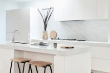 a minimalist neutral kitchen with sleek cabinets, a white marble backsplash and countertops, woodne stools and a skylight