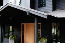 a modern Nordic front door porch with concrete planters with greenery and a rug is very chic