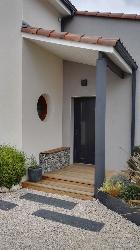 a modern and laconic front door porch with a bench with rocks inside, greenery in pots and a stylish door