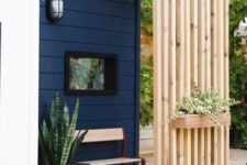 a modern and simple private porch with a slab screen, a wooden chair and some potted plants is veyr welcoming