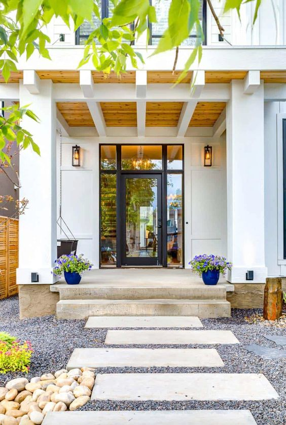 a modern bright porch with a wooden ceiling with beams, a hanging metal chair, purple blooms in pots