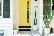 a modern desert porch with potted cacti, mosaic tiles on the porch and a bright sunny yellow door