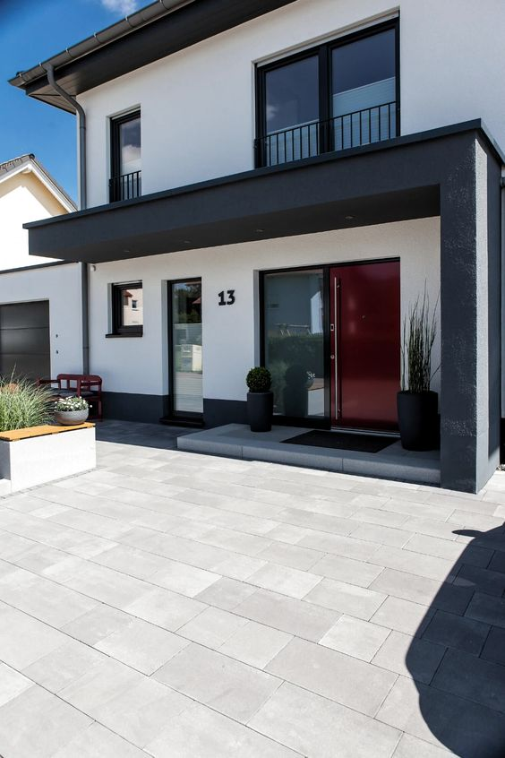 a modern entrance with black planters with greenery, a bench with a cushion and some greenery