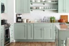 a modern farmhouse kitchen in pastel green, with a white tile backsplash and some wicker touches