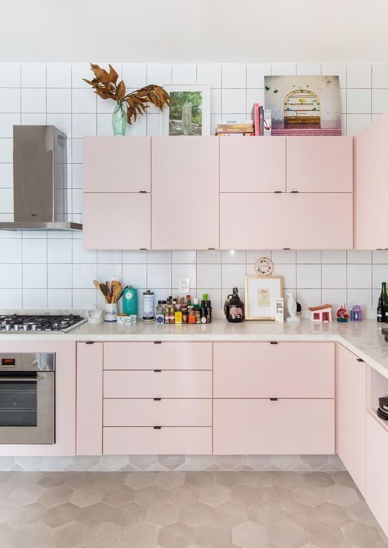 a modern kitchen in light pink, with a white tile backsplash and built-in appliances is all the chic