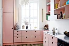 a modern kitchen in pink, with sleek cabinets, a catchy chandelier and a green tile floor is very bold