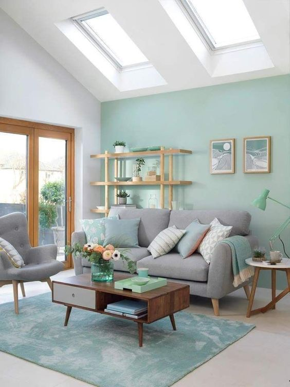 a modern living room with a light green accent wall, a green rug and a lamp, green pillows and accessories