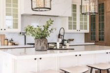 a modern neutral farmhouse kitchen with a white marble backsplash, countertops and a hood, glass uppers, pendant chandeliers