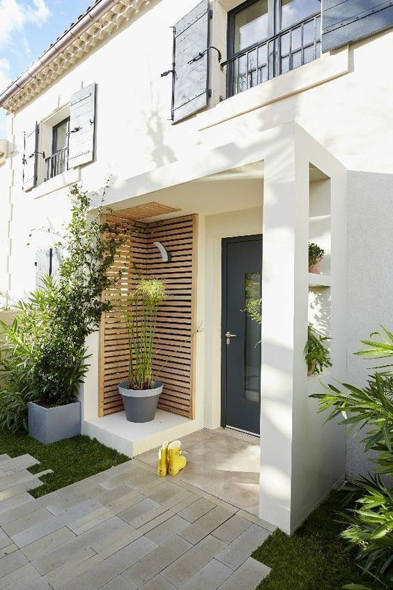 a modern porch with wooden slab screens, greenery in pots and mustard rubber boots