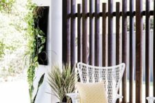 a modern private porch with a striped rug, a white woven chair, bright mustard touches and greenery