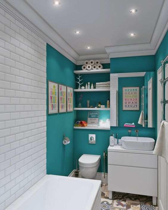 a modern small bathroom with turquoise walls and white subway tiles plus white appliances for a contrast